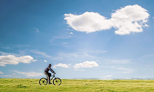man riding bicycle across field