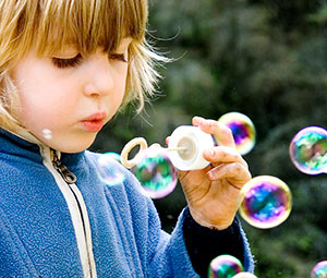 young girl blowung bubbles