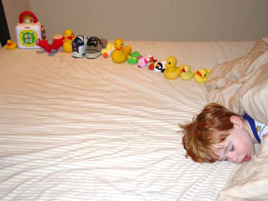 boy sleeping in a bed with ducks and toys lined up in a row