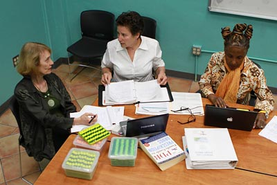 Melinda, Renita, and Wanda sitting at a table with their case folders, books and remedies