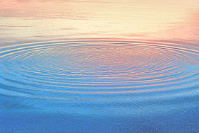 ripples on water with peach colored reflections