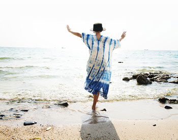 woman doing yoga tree pose in blue and white tie dye dress and sunhat on a beach
